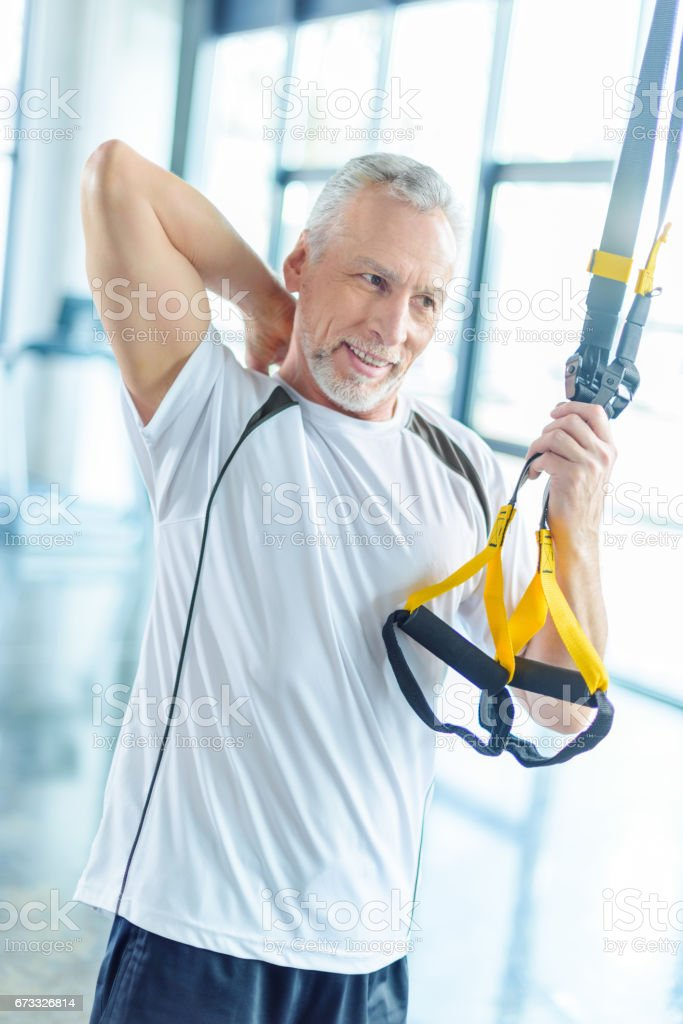 senior sportsman training with resistance band in sports center stock photo