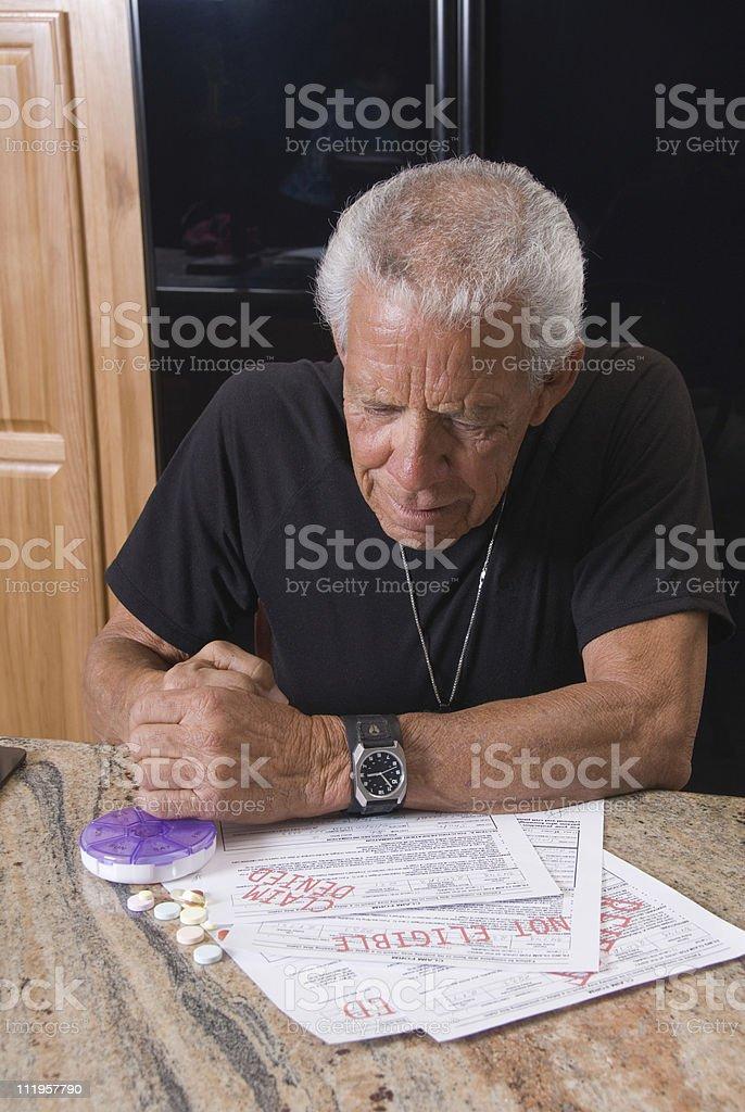 Senior staring at his denied medical bills stock photo