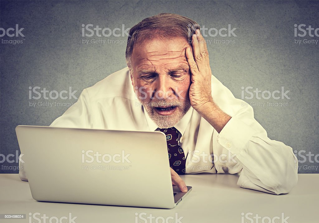 senior stressed man working on laptop sitting at table stock photo