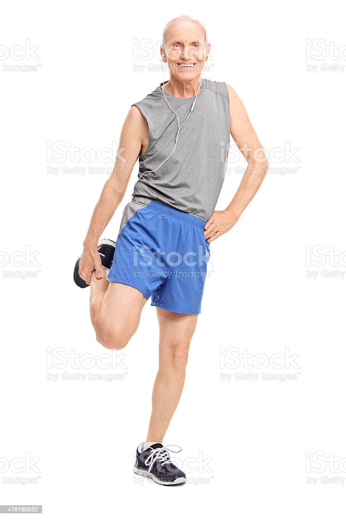Senior stretching his leg and listening music stock photo