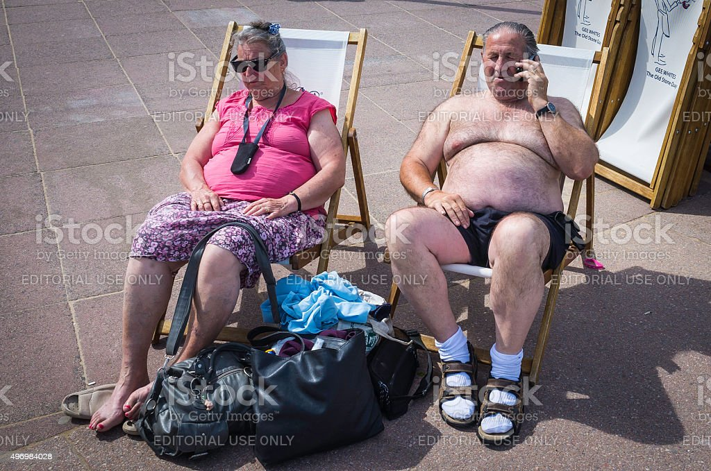 Senior sunbathers enjoying seaside sunshine on beach promenade deckchairs Dorset stock photo