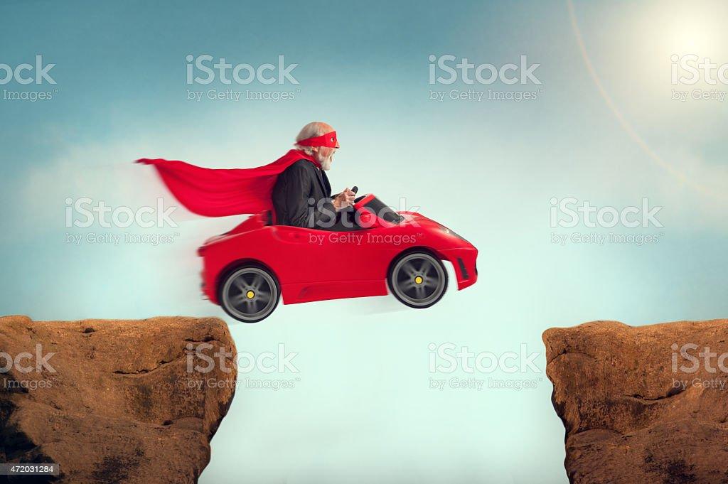 senior superhero driving a car off a ravine stock photo