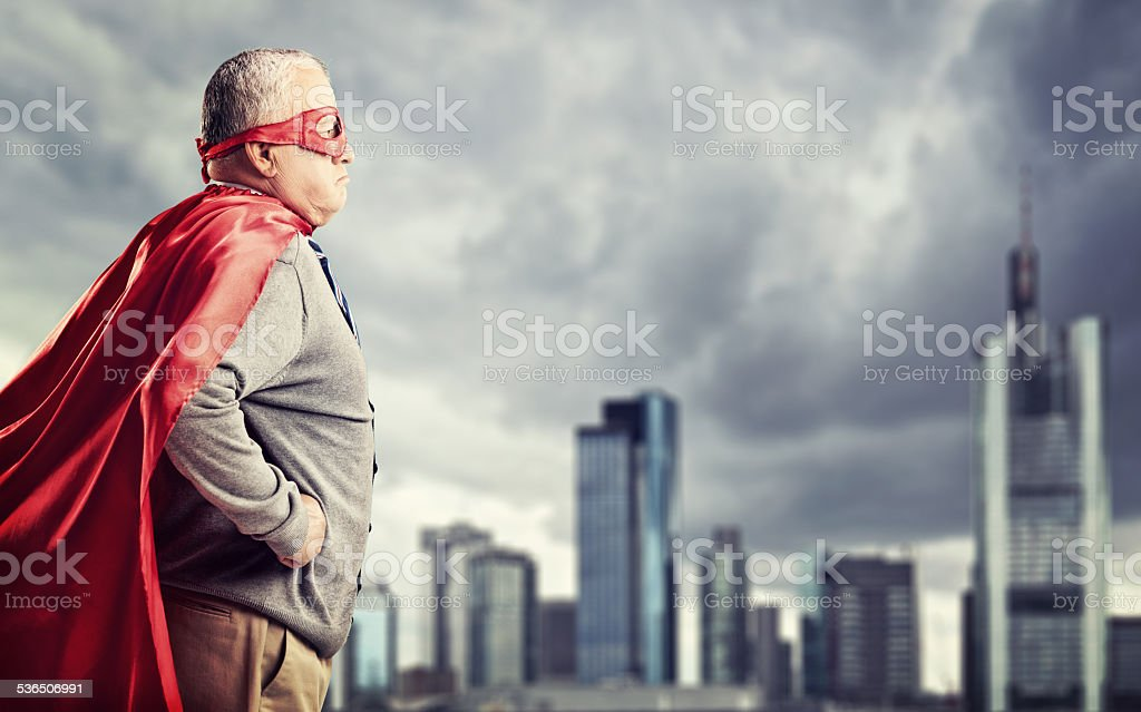 Senior superhero standing in front of a city stock photo