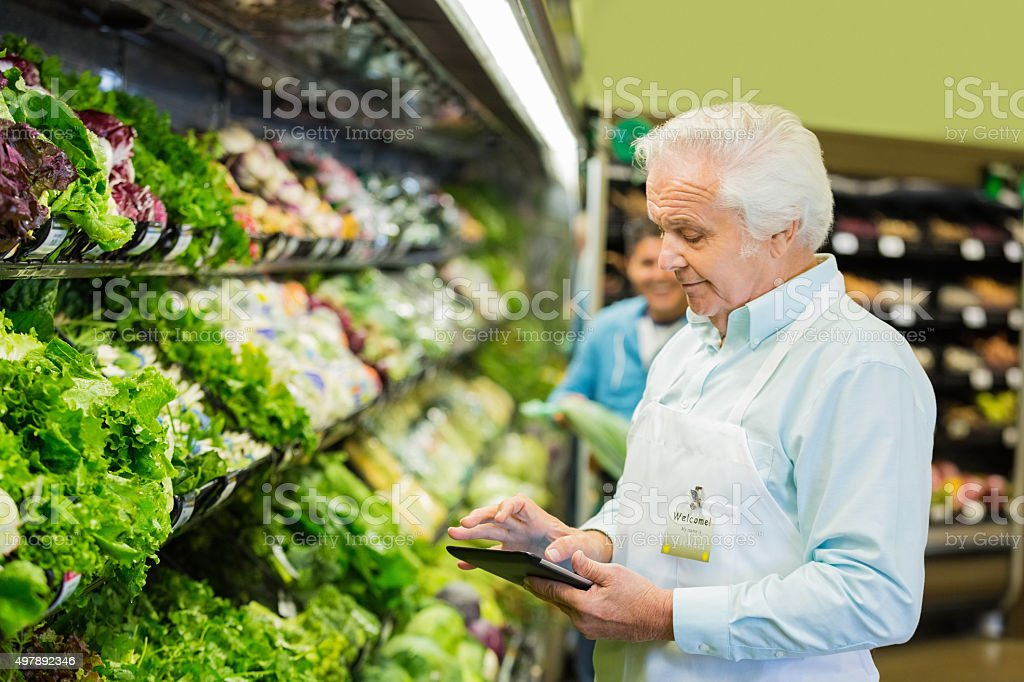Senior supermarket manager or employee taking inventory in produce section stock photo