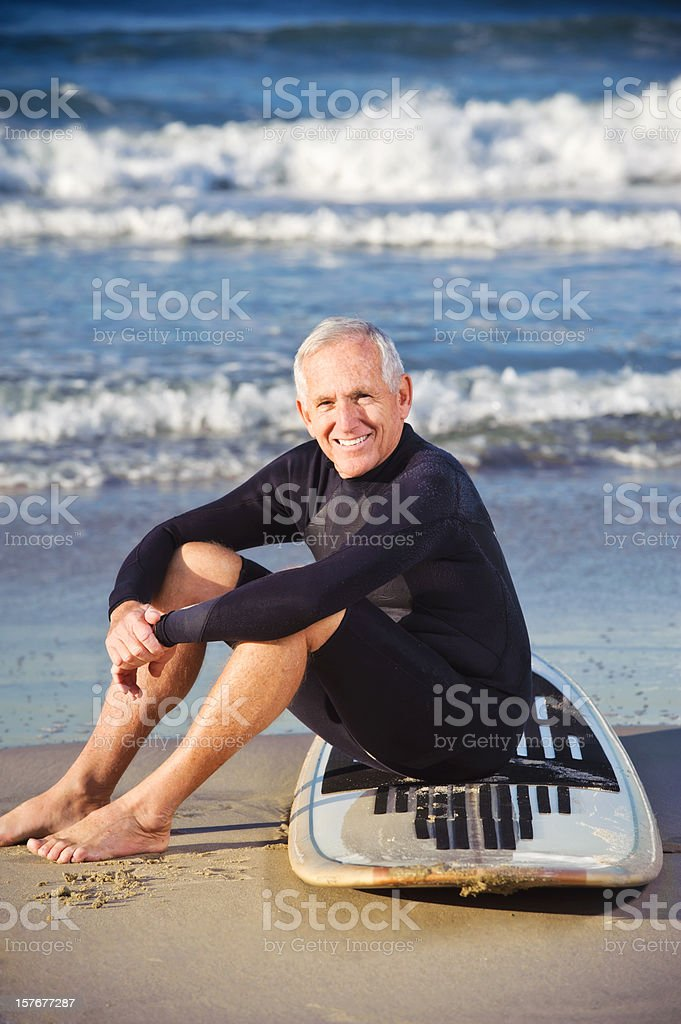 senior surfer smiling and sitting on surfboard royalty-free stock photo