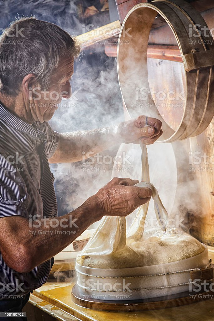 Senior Swiss Farmer making cheese stock photo