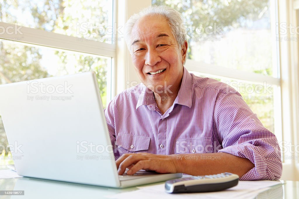 Senior Taiwanese man working on laptop royalty-free stock photo