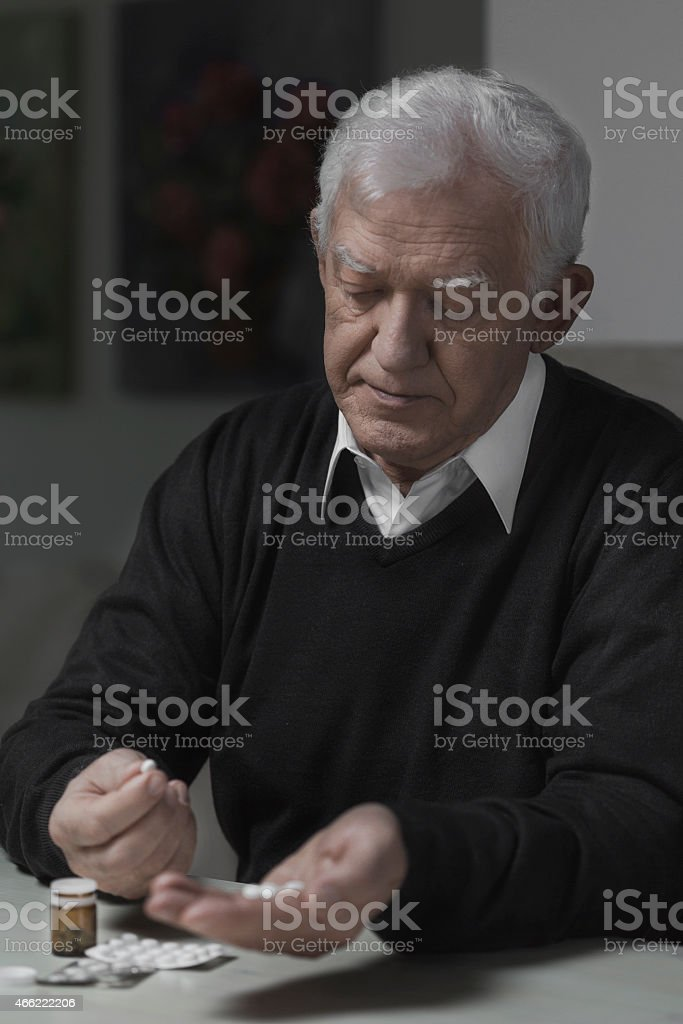 Senior taking pills stock photo