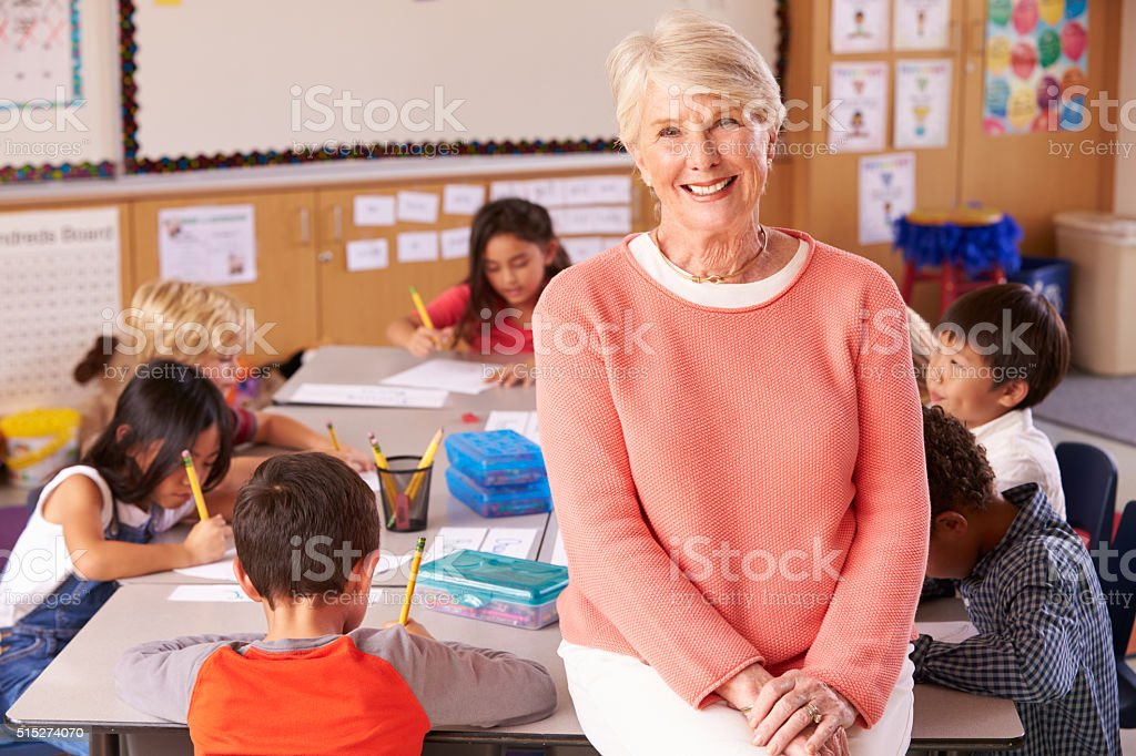 Senior teacher in classroom with elementary school kids stock photo