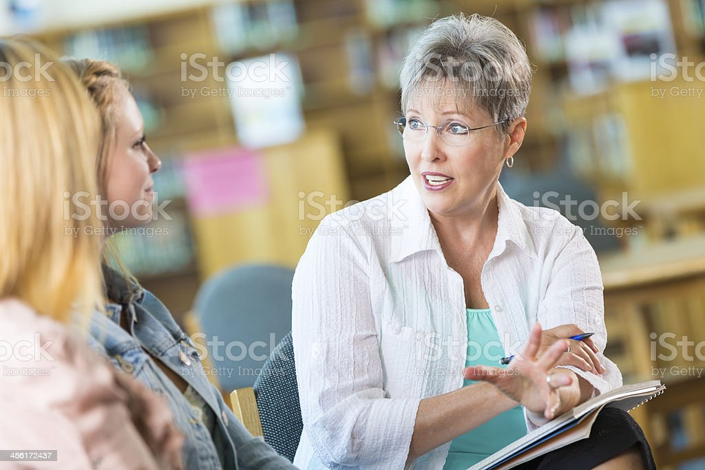 Senior teacher or principle meeting with student and parent stock photo