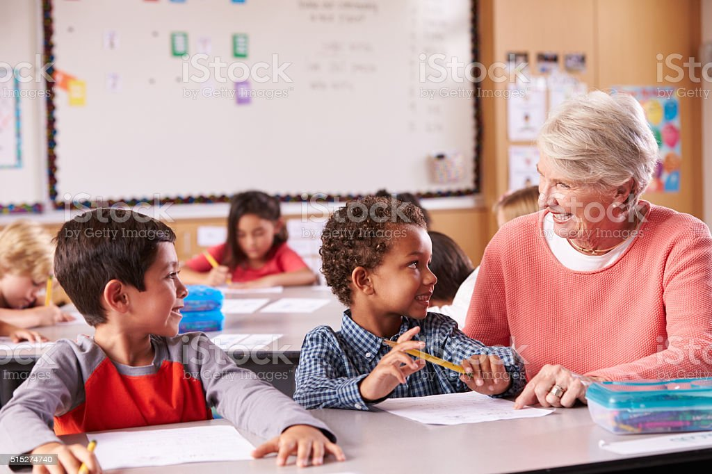 Senior teacher sitting with elementary school kids in class stock photo