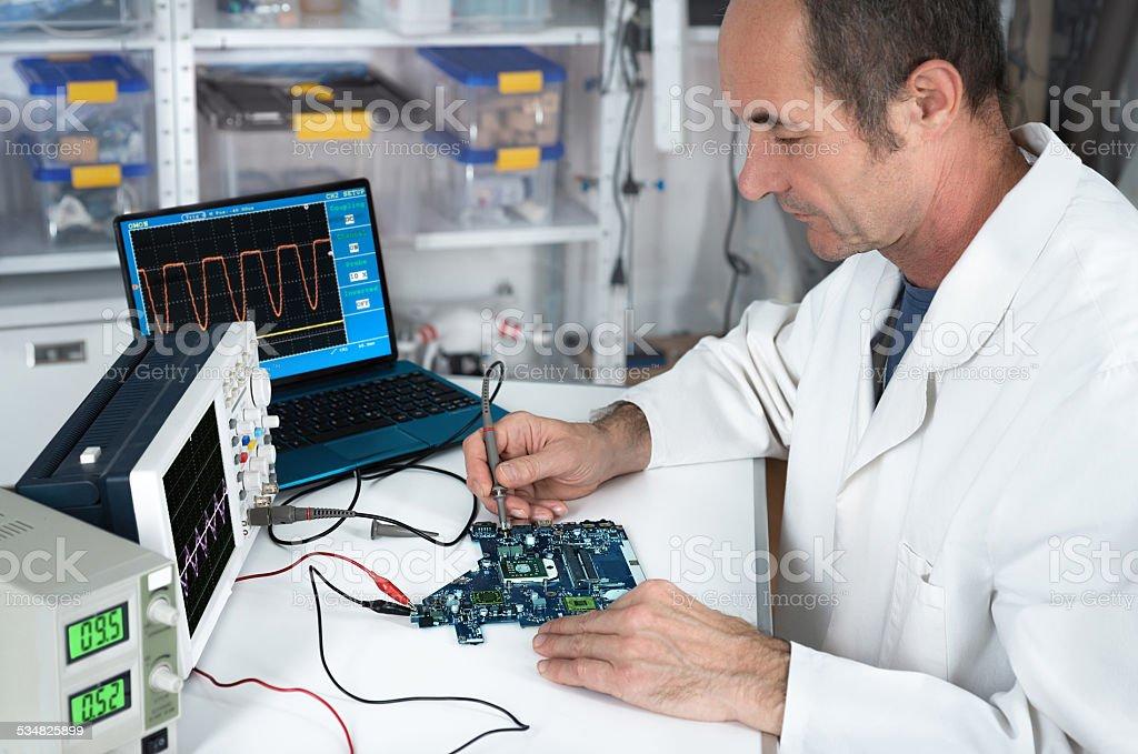 Senior tech works in hartware repair facility stock photo