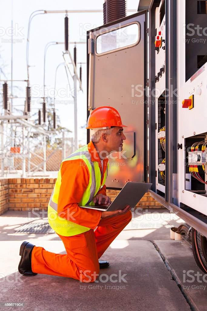 senior technician checking computerized transformer stock photo