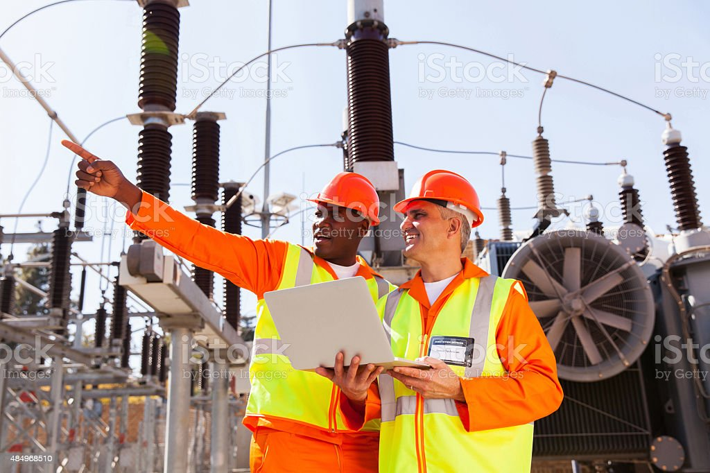 senior technician with co-worker working together stock photo