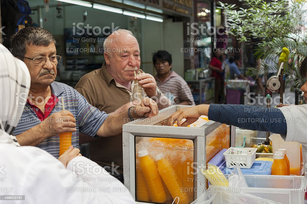 Senior Thai men buying fresh orange juice on Bangkok street. royalty-free stock photo