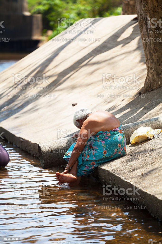 Senior Thai woman is washing her feet stock photo