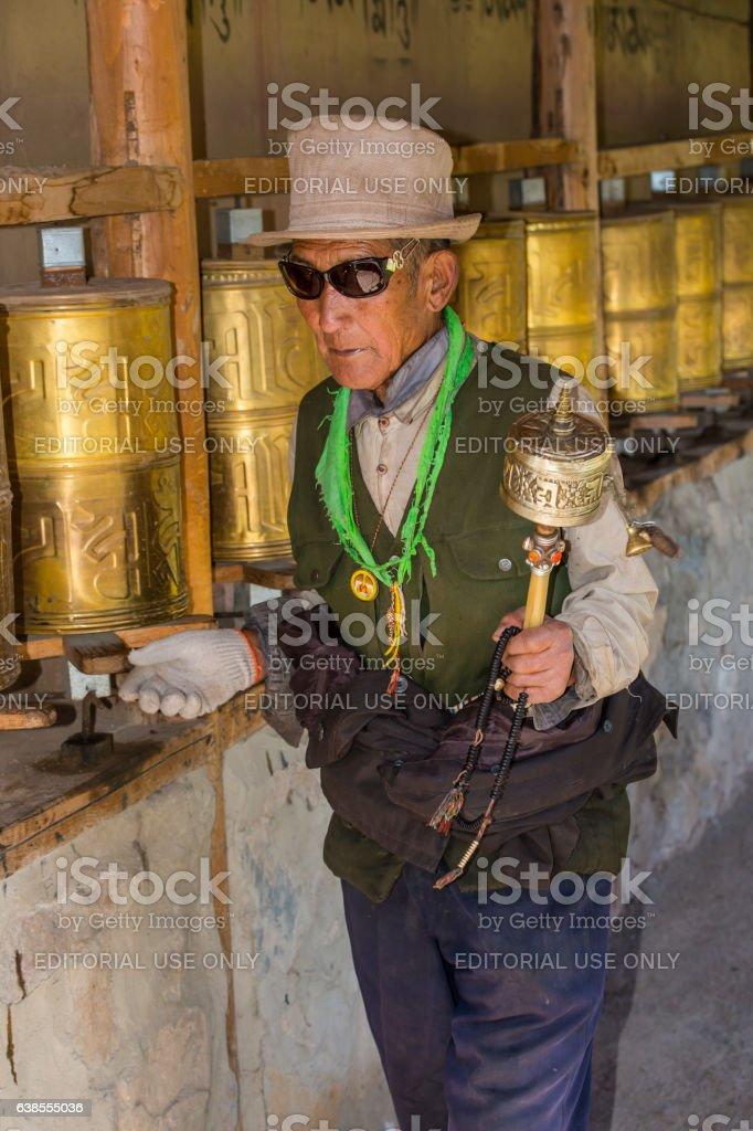 Senior Tibetan man is turning prayer wheels stock photo