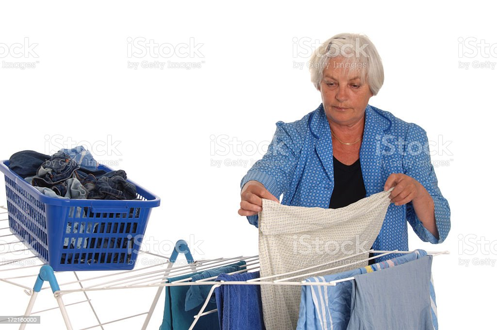 Senior tired housewife with laundry rack stock photo