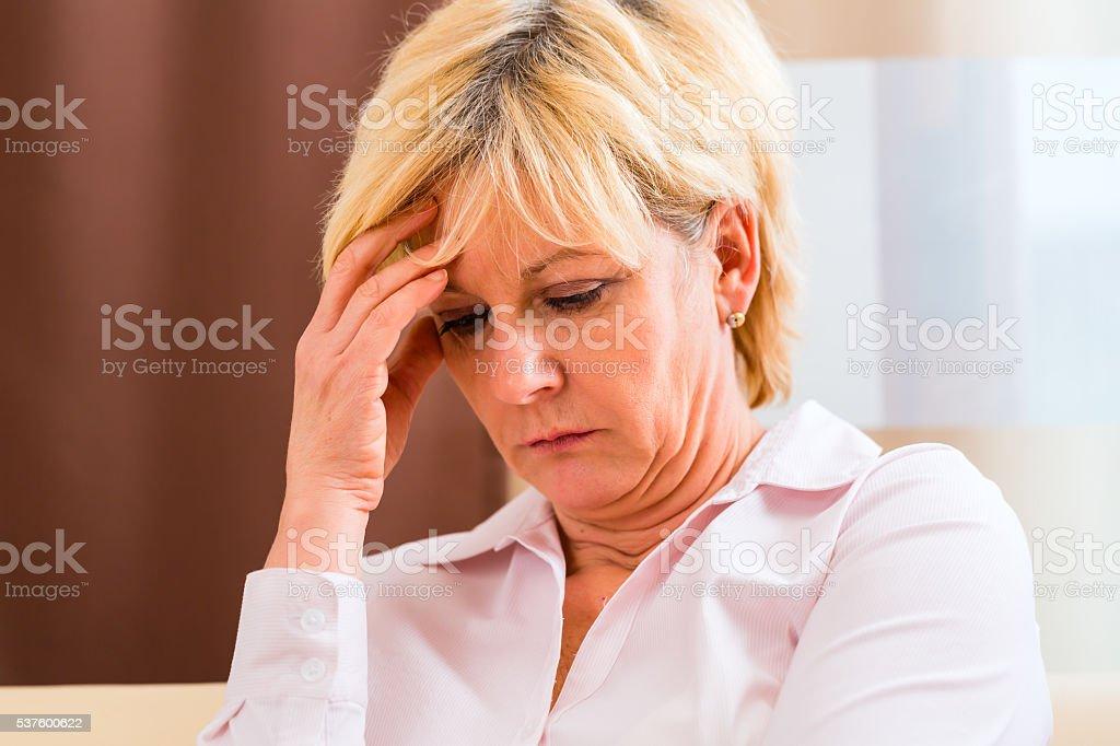 Senior touching forehead having headache or pain stock photo