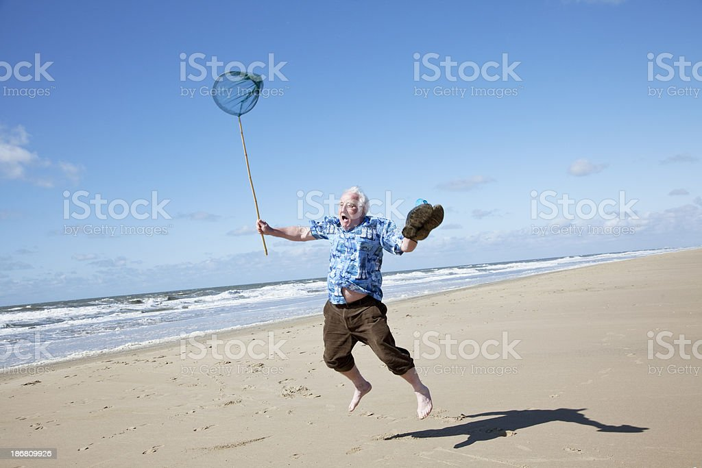 senior tourist at the beach jumping stock photo