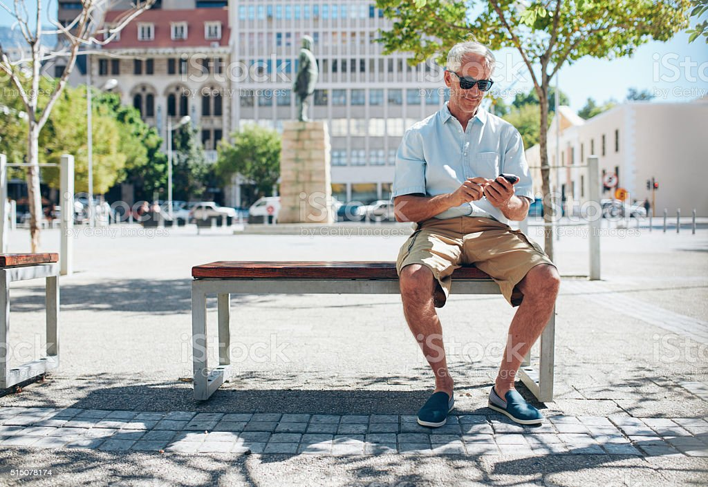 Senior tourist in the city using mobile phone stock photo