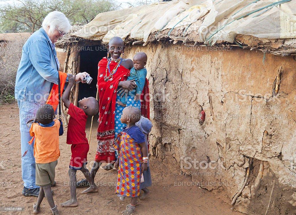 Senior tourist visiting family in maasai village. royalty-free stock photo