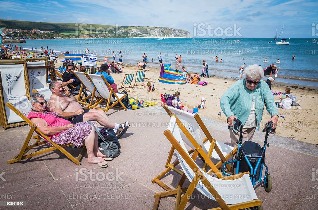 Senior tourists enjoying sunshine deckchairs at busy seaside beach England stock photo