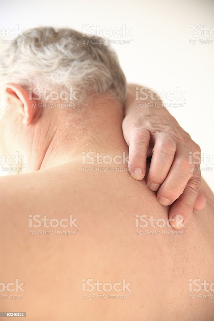 Senior tries to scratch his bare back stock photo