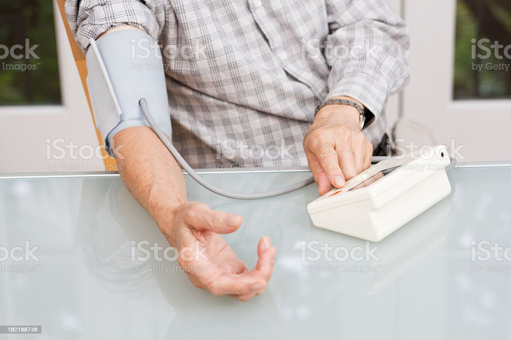 Senior Using Blood Pressure Gauge, Monitoring Healthcare Vitals at Home royalty-free stock photo