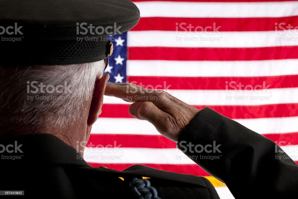 Senior veteran man in military uniform saluting American flag stock photo