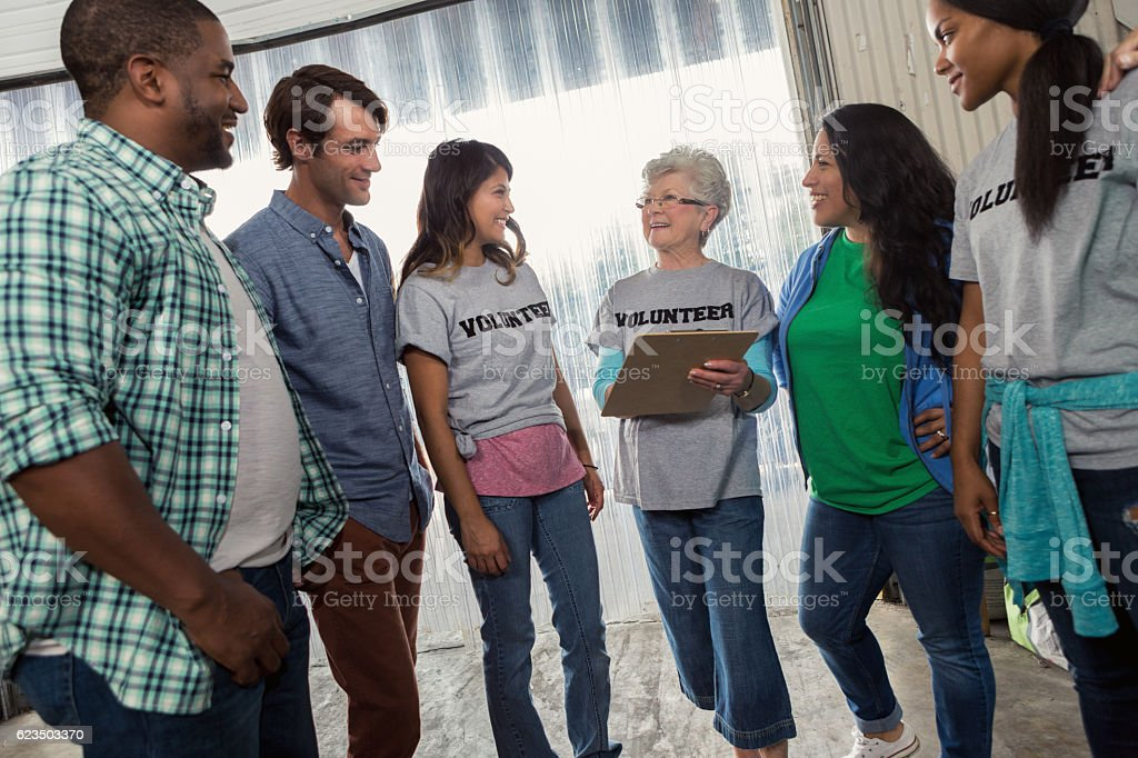 Senior volunteer coordinator gives assignments to volunteers stock photo