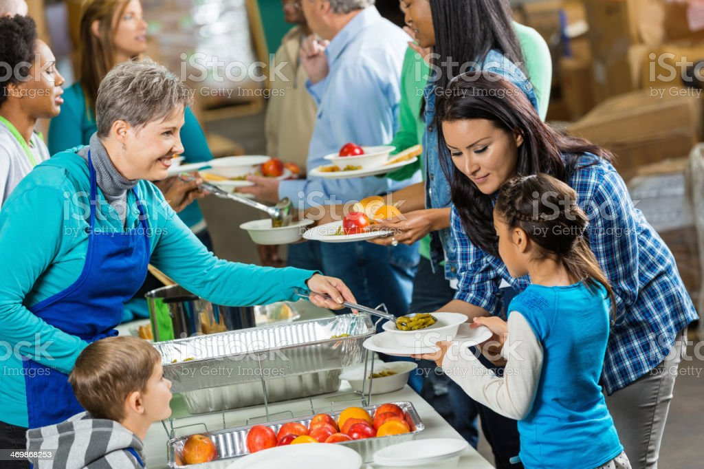 Senior volunteer serving healthy meal to family at soup kitchen stock photo