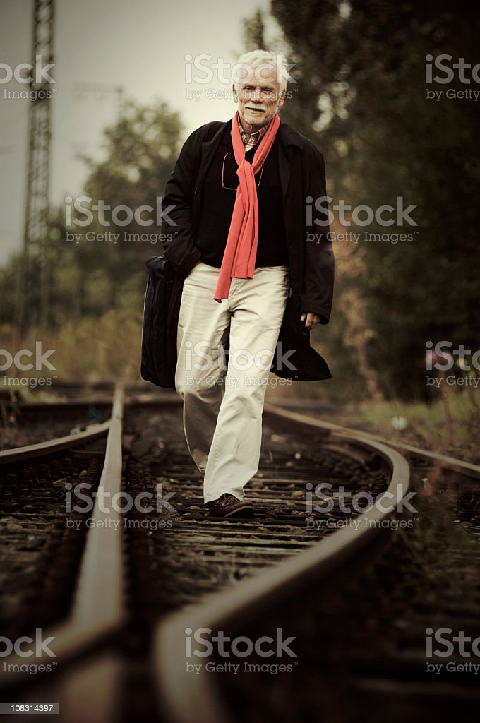Senior walking on the tracks stock photo