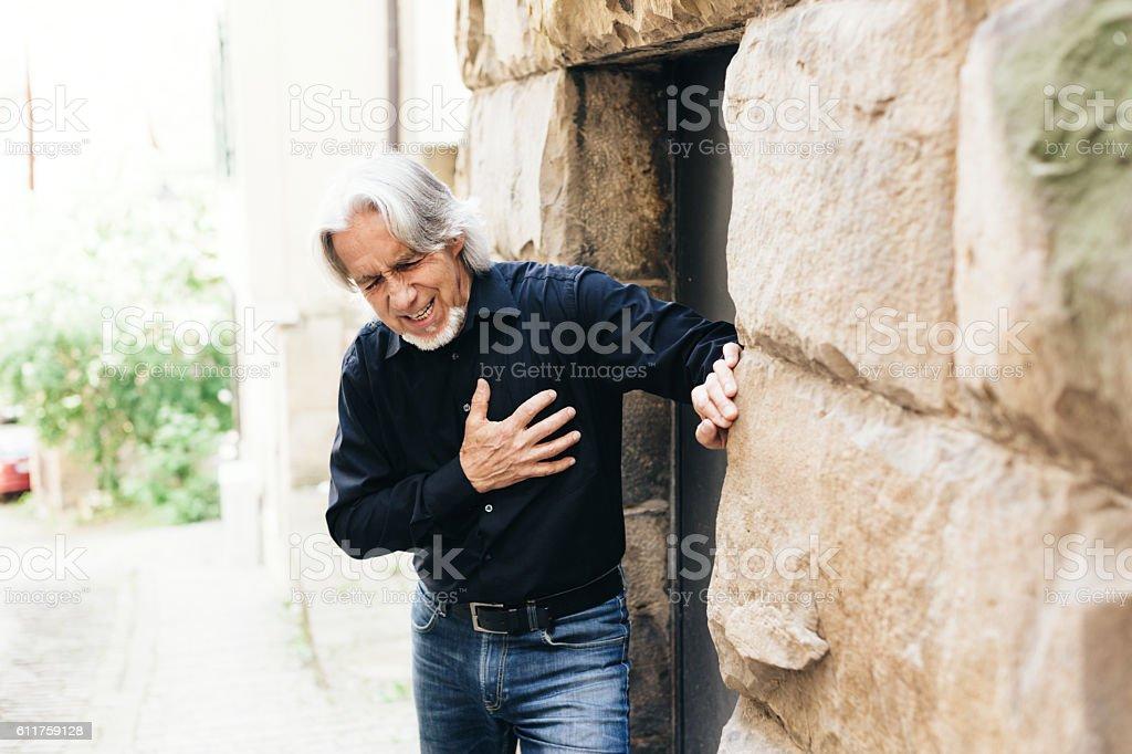 Senior walking through city, having heart attack stock photo