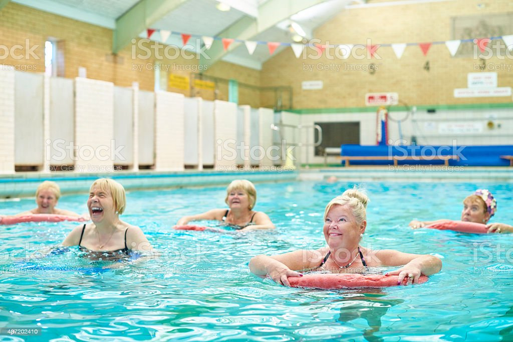 senior water aerobics using pool noodle stock photo