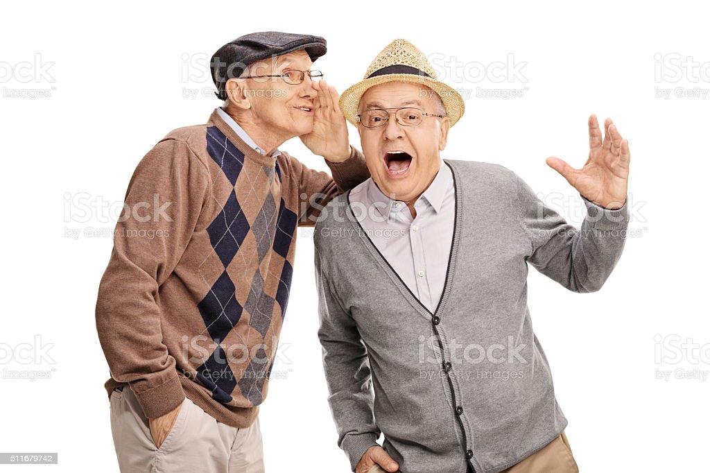 Senior whispering something to his friend stock photo