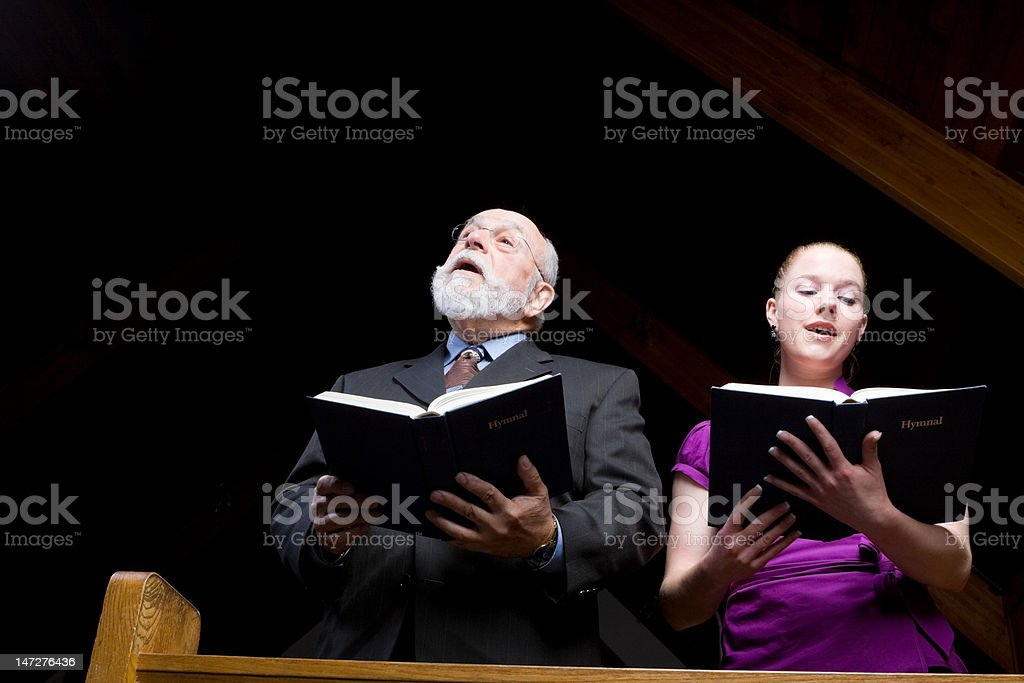 Senior White Man Young Woman Singing in Church Holding Hymnals stock photo