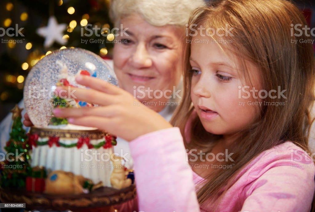 Senior with girl watching christmas snow globe stock photo