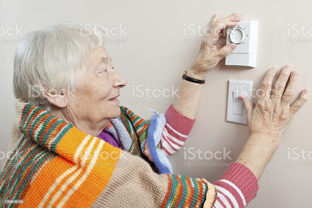 Senior woman adjusting her thermostat royalty-free stock photo