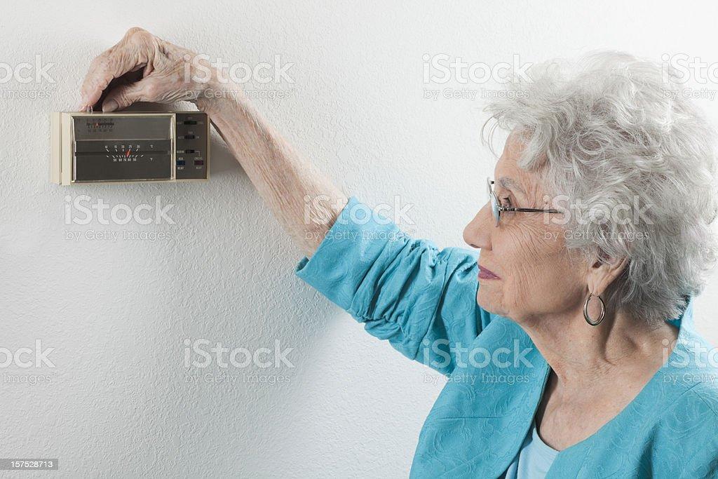 senior woman adjusting home thermostat royalty-free stock photo