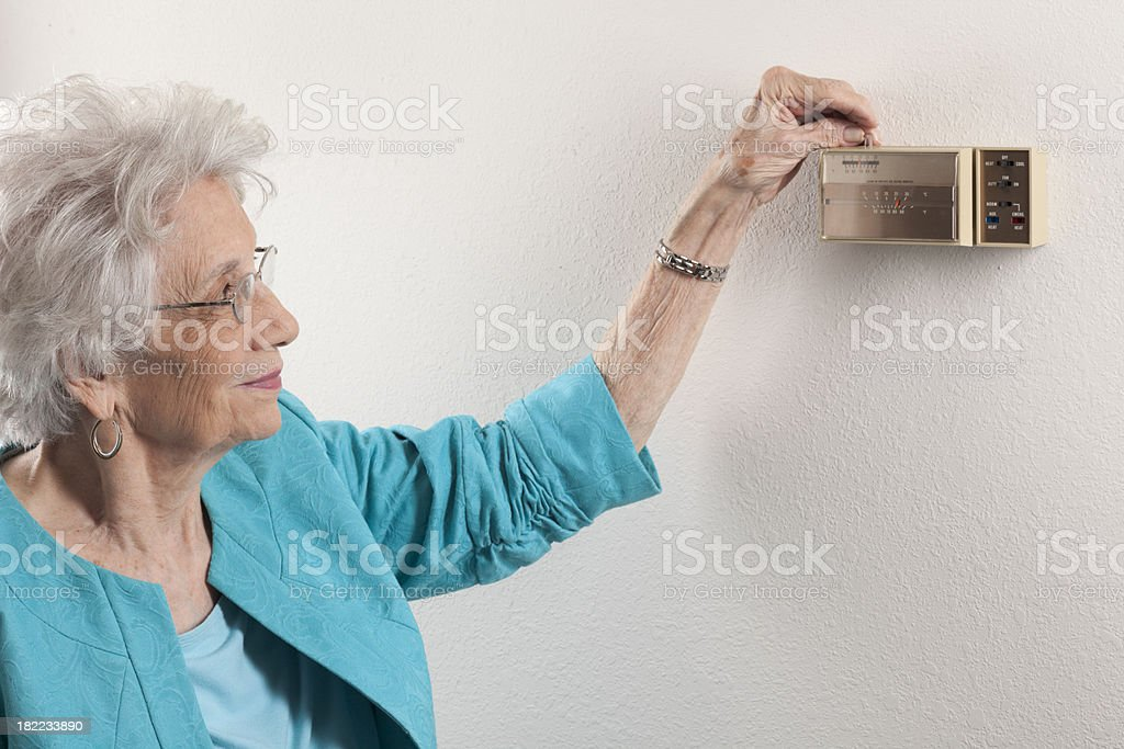senior woman adjusting home thermostat stock photo