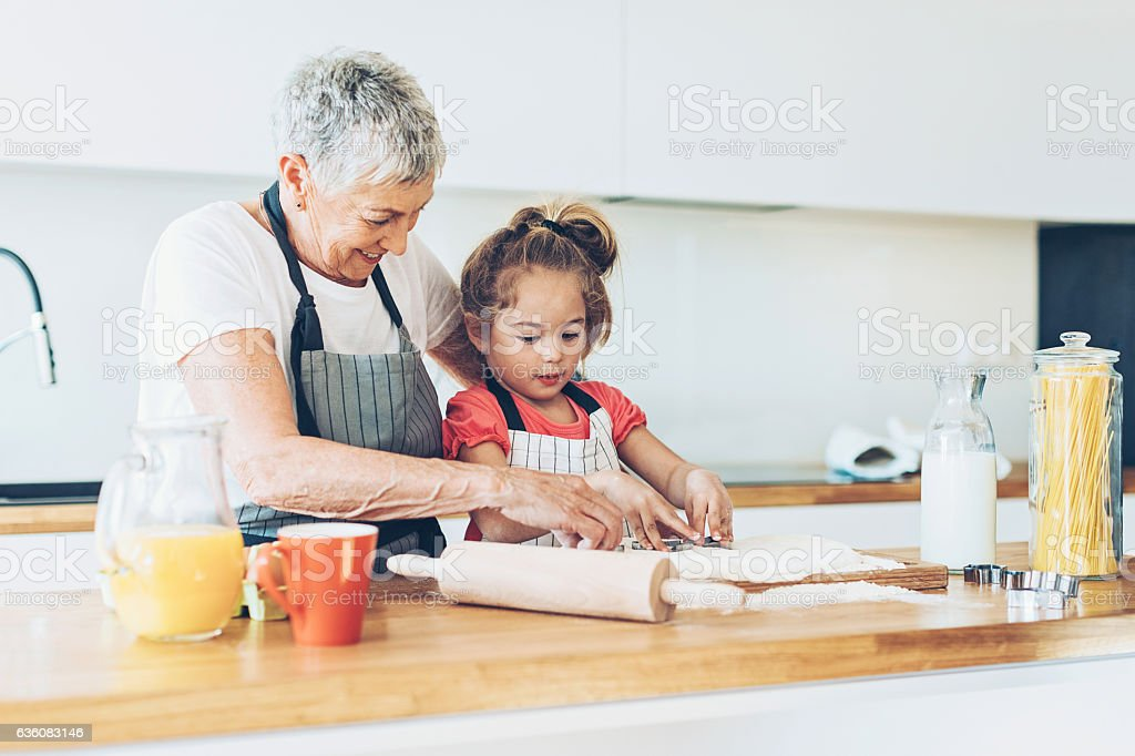 Senior woman and a small girl making cookies stock photo