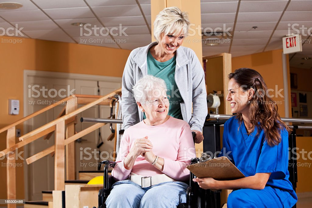 Senior woman and adult daughter talking to physical therapist royalty-free stock photo
