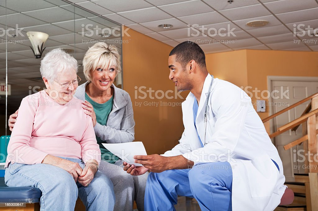 Senior woman and adult daughter talking to physical therapist stock photo