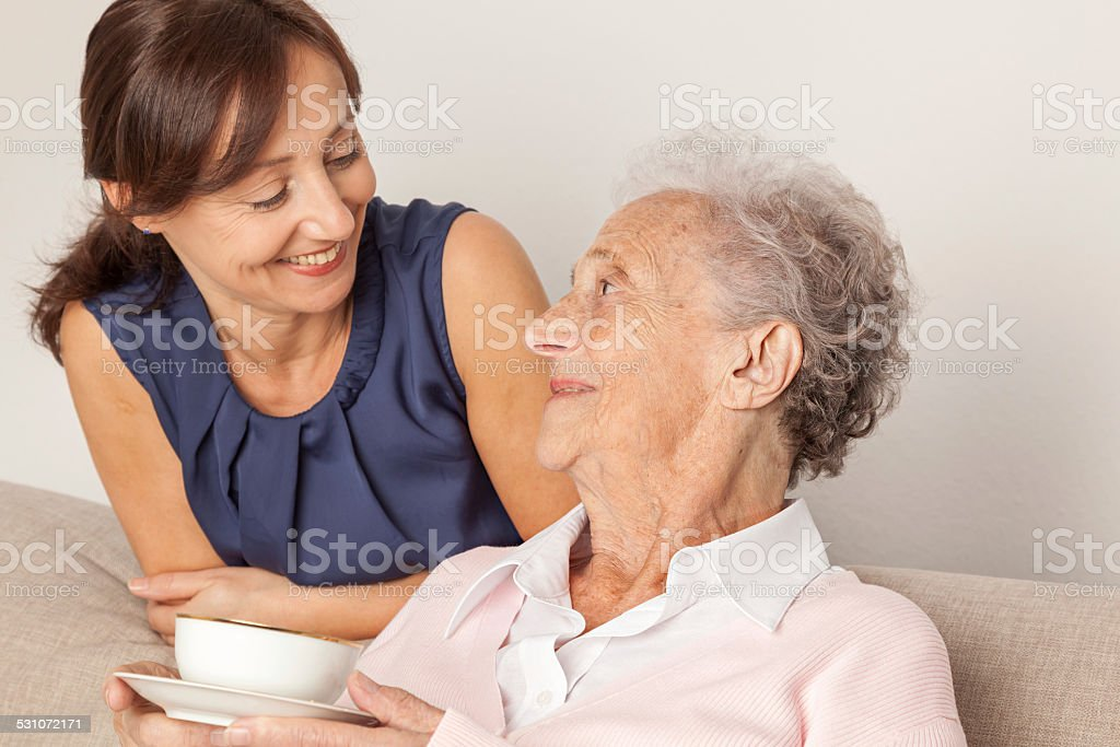 Senior woman and caregiver at home stock photo