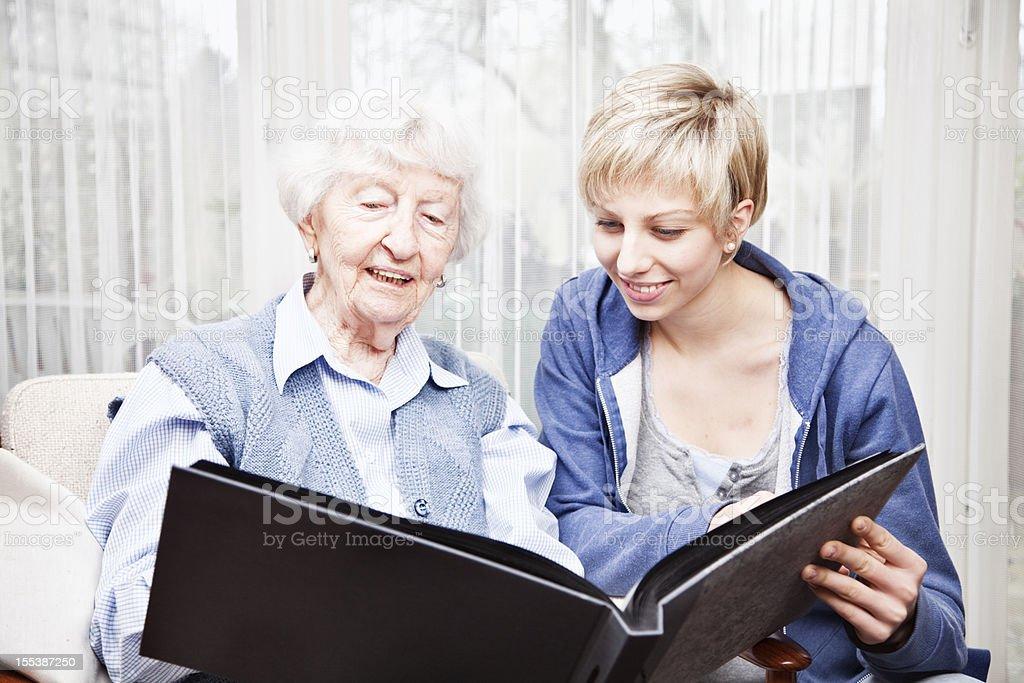 senior woman and caregiver sharing memories royalty-free stock photo