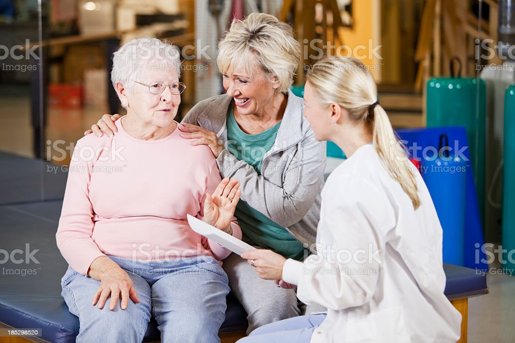 Senior woman and daughter talking to physical therapist stock photo
