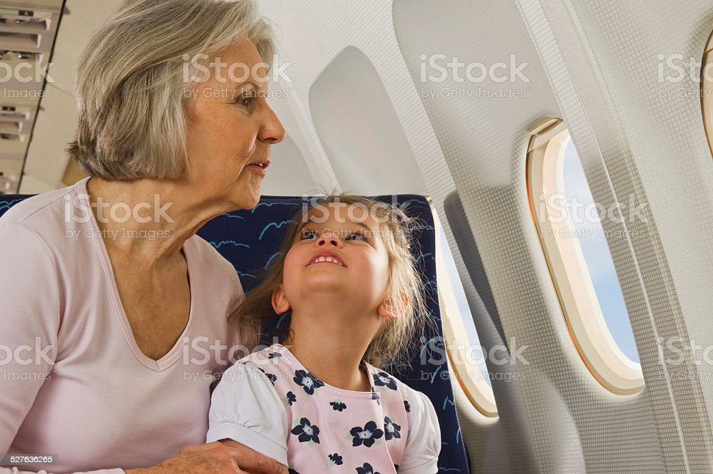 Senior woman and girl looking through window  on airplane stock photo