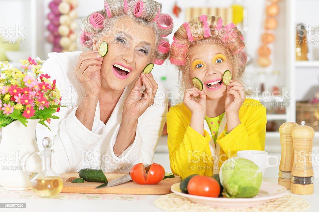 Senior woman and granddaughter at kitchen stock photo
