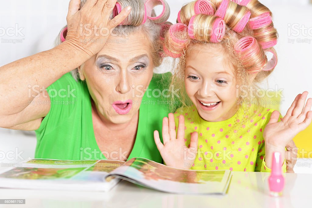 Senior woman and granddaughter painting nails stock photo